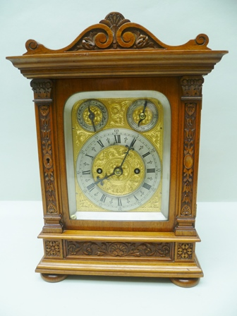 AN EDWARDIAN WALNUT CASED EIGHT DAY MANTEL CLOCK fitted twin fusee chiming movement, the case with carved bell husk decoration, the engraved gilded face with silvered chapter ring with Roman hours and Arabic minutes, having strike/silent and regulation indicators, on bun feet, case 35cm high