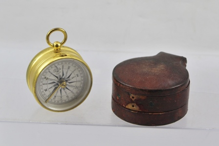A VICTORIAN GILT BRASS TRAVELLERS POCKET COMPASS, having ring top, silvered calibrated dial compensated and original red leather case