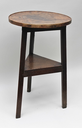 A 19TH CENTURY OAK CRICKET TABLE, having banded gallery top with fitted undertier, top 41cm diameter