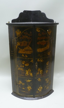AN EARLY 19TH CENTURY LACQUERED CHINOISERIE DECORATED BOW FRONTED HANGING CORNER CUPBOARD, possibly mahogany with later paint effect, 106cm high including upstand
