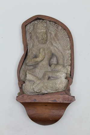 A CARVED LIMESTONE BODHISATTVA considered to be 18th century Hindu Indian Deity in a meditative pose, right hand raised, with part of a decorative surround remaining, mounted within purpose made wooden frame, statue 41cm high