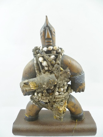 A NKONDI FETISH IDOL from The Congo region of Equatorial Africa, carved wood with beads and bone, overall 25.5cm high, standing upon a later made exhibition base  (Nkondi means hunter, they hunt down and attack wrong-doers, witches or enemies) together with a CENTRAL AFRICAN, LUBA OR BAKONGO TRIBE, CARVED WOOD RITUAL BELL, having a kneeling female form knop handle, the bell with masks to either side (The bell is considered to be a Royal or status symbol, rather than a musical instrument), bears paper label Bakongo Zaire), 30cm high