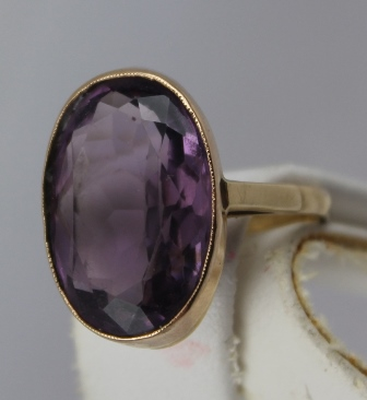 AN AMETHYST SET GOLD DRESS RING, the rub over setting stamped 9ct, set with an oval amethyst, size S