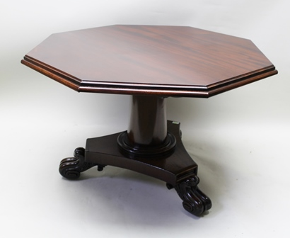 A 19TH CENTURY REGENCY DESIGN MAHOGANY SUPPER OR CENTRE TABLE, having octagonal snap-top, on tapering plain stem and triform platform base with substantial scroll feet, 112cm wide