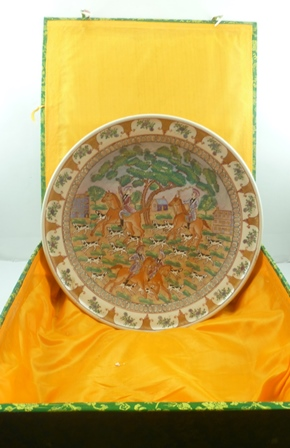 A LARGE CHINESE CHARGER having polychrome painted European hunting scene, within a floral trellis border, bears character marks verso, 48cm diameter, in decorative fabric covered box