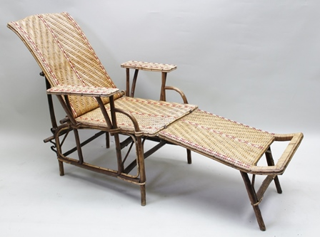 AN EARLY 20TH CENTURY BAMBOO FRAMED RATTAN LOUNGER, having adjustable racking back, broad arms, with removable leg rest, natural colours but inset with a decorative red and white stripe