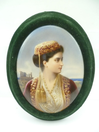 A CIRCA 1900 VIENNA STYLE OVAL PAINTED PORCELAIN PLAQUE, depicts a bust length profile portrait of a young Grecian woman dressed in opulent robes, a classical ruin in the landscape, monogrammed I.H., 18cm x 13cm mounted within an oval green velvetframe