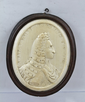 AN EARLY 18TH CENTURY RELIEF CARVED IVORY PORTRAIT MINIATURE OF ARENT FURLEY (Secretary to General Stanhope, 1708-1711, and the Earl of Peterborough in Spain) he died in 1705. Arent was the son of Benjamin Furley (1636-1714) Quaker, a friend of Fox,Penn and Locke. Arent is depicted in carved shallow relief, shoulder length bust profile, wearing a long powdered wig, a draped garment over plate armour, the arm is carved with the letters I.M.? possibly the sculptor, around the oval is carved the text .A:FVRLY.NATVS.1685.AE TATIS.SVAE.XXIII., the ivory panel is set into a mahogany frame bearing hand written label verso - Concerning Arent and his father Benjamin, ivory panel - 10.5cm x 8.5cm