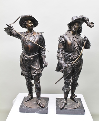 A PAIR OF 20TH CENTURY BRONZE FIGURES MODELLED AS 17TH CENTURY CAVALIERS with drawn swords and broad brimmed feather trimmed hats, raised upon marble plinth bases, 87cm high