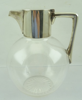 HUKIN AND HEATH A CHRISTOPHER DRESSER DESIGN SILVER MOUNTED CLARET JUG with fluted and hinged cover, plain glass body with star cut base, Birmingham 1890, 17.5cm high