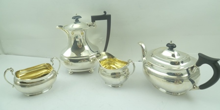 A MATCHED SILVER TEA SET of Georgian design, comprising teapot, milk jug, and a two-handled sugar bowl, the latter two with gilded interiors, engraved band decoration, the teapot made by Sydney Hall & Co., Sheffield 1931, the milk jug and sugar bowlby Sibray, Hall and Co. Ltd., Sheffield 1927 and 1928, together with a SILVER HOT WATER POT by William Griffiths & Sons, of waisted form with gadrooned rim, on bun feet, Birmingham 1938, combined weight of all four items, including the non-silver handles and knops 1686g.
