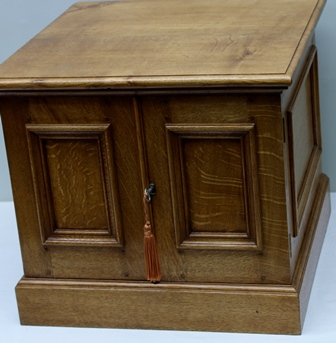 JOHN NETHERCOTT FOR FELIX DENNIS  A BESPOKE OAK CABINET of box form, having plain top, panelled sides, twin panel doors opening to reveal shelved interior the whole supported on a plain plinth base, 42cm x 48cm (this unit was purpose built in 1999 and supported the fax/printer in his private office)