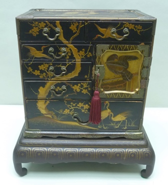 A PROBABLY 19TH CENTURY ORIENTAL LACQUER WORK TABLE CABINET, having multi-drawer frontage, some concealed behind single cupboard door, decorated in the round with cranes and other birds on blossoming boughs, supported on a four-legged table base, the whole standing 38cm high