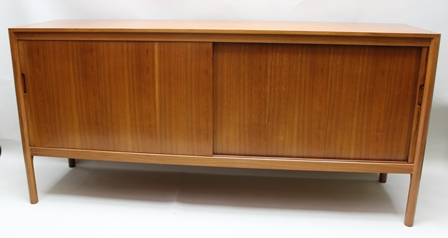 A GORDON RUSSELL AMERICAN BLACK WALNUT LONG AND LOW SIDEBOARD, with twin sliding doors revealing a well-fitted cherry wood interior, supported on octagonal chamfered uprights, bearing the manufacturers label on verso, designed by W.H. Russell and hand built by B.A. Jones February 1963, model no. R423, 87cm high x 183cm long
