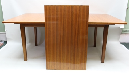 A GORDON RUSSELL AMERICAN BLACK WALNUT RECTANGULAR TOPPED EXTENDING DINING TABLE, having single central extra leaf, supported on four square formed chamfered legs, bearing makers label, designed by W.H. Russell and hand made by L.M. Pratt in February 1963, together with a SET OF EIGHT FOYER / RECEPTION CHAIRS, comprising six singles and two arm chairs, on angular jointed wooden frames, the table 72cm high x 96cm deep x 183cm long (closed) plus extra leaf of 61cm
