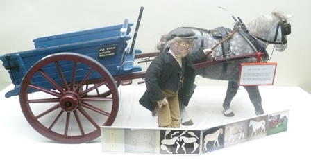 A & E STARLEY OF COVENTRY, WARWICKSHIRE A MODEL OF A TIPPING CART, painted in blue and burgundy, contains various agricultural hand tools, scythe, pitchfork etc., with draught horse modelled on the Percheron, together with a dressed MODEL FARM WORKER in cord trousers, waistcoat with watch chain, flat cap, he stands, 46cm high (believed to be one-quarter scale)