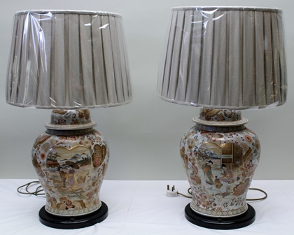 A PAIR OF PORCELAIN BASED TABLE LIGHTS, hand painted with Oriental scenes of domestic life, stylised flower heads and butterflies, on ebonised circular plinth bases, together with pleated taupe linen effect shades, each standing 78cm high overall