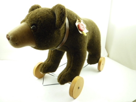A HERMANN PULL-ALONG BEAR ON WHEELS no. ?30607, with brown and black safety eyes and brown stitched nose and mouth, covered all over in plush dark brown mohair with contrasting mushroom coloured mohair muzzle and pads to feet, the feet attached to achromed frame with four wooden wheels and provision for string to pull-along or to ride the bear, having a brown collar, complete with label sewn into tummy, paper labels and red Hermann Teddy Original seal attached to shoulder, 40cm high x 62cm long (from nose to tip of tail)