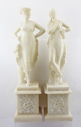 A PAIR OF LATE VICTORIAN CARVED ALABASTER STATUES depicting young women in the classical style, wearing diaphanous costume, standing upon plinth column bases carved with musical trophy decoration, 66cm high