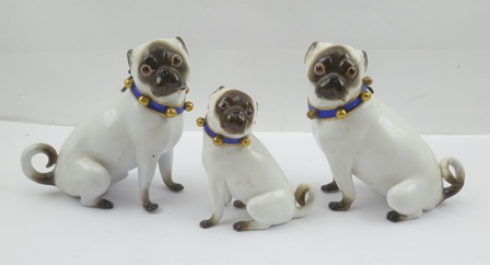 A PAIR OF MEISSEN PORCELAIN PUG DOGS, circa 1880, modelled in the manner of J.J. Kaendler, each with a blue tied ribbon effect collar mounted with gilded bells, blue crossed swords and incised marks to base, 13.5cm high, together with ONE OTHER SIMILAR seated porcelain pug bitch, 10cm high