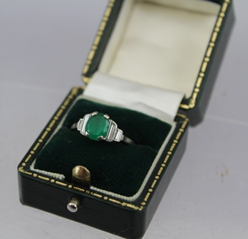 AN 18CT WHITE GOLD RING set with central emerald flanked by baguette cut diamonds, ring size K, in green vendors case