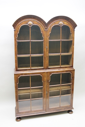 A DUTCH DESIGN MAHOGANY DISPLAY CABINET, having double arched top with scallop shell decoration, fitted two squared glazed doors over a base fitted with two matching glazed doors, raised on bun feet, 190cm high x 113cm wide