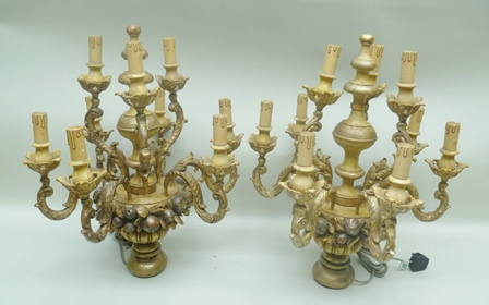 A PAIR OF CONTINENTAL CARVED GILT WOOD TABLE CANDELABRA, having six lower and three upper branches, on bases of fruit and foliage, 63cm high