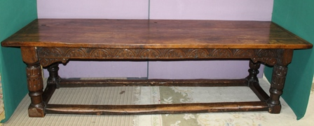 A PART 18TH CENTURY OAK REFECTORY DINING TABLE, having plank top over lunette carved frieze with acanthus scroll cheeks, over fluted stylised cup and cover supports united by plain stretchers, 259cm x 83cm