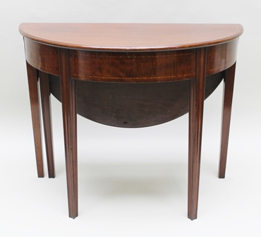 A 19TH CENTURY MAHOGANY DEMI-LUNE SIDE TABLE, inlaid line decoration, with matching frieze, fitted drop leaf to the rear, forming a circular breakfast or centre table, raised on squared fluted tapering supports, 92cm wide