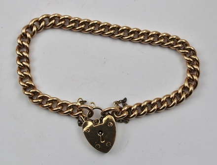 A 9CT ROSE GOLD CURB LINK BRACELET with padlock clasp, 21g.