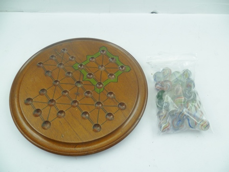 A MAHOGANY SOLITAIRE BOARD with 32 hand-made MARBLES