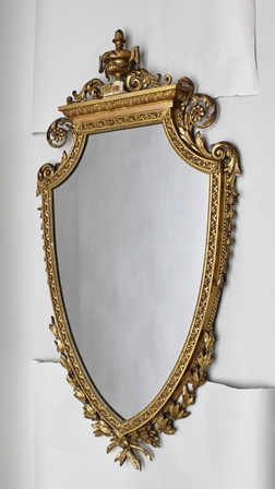 A 19TH CENTURY GILT FRAMED WALL MIRROR, of shield form with swagged urn finial, frieze of acanthus leaves with graduated bell husks to the sides and a laurel wreath at the base, overall 130cm high
