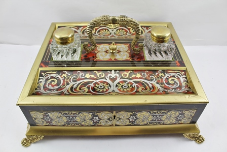 A 19TH CENTURY BOULLE WORK STANDISH OR DESK INKWELL, fitted central handle over a lidded compartment, flanked by brass lidded glass inkwells, a pen tray either side, the base fitted one rosewood lined drawer, the base with gilded mask decoration, raised on based fitted cast paw feet, top section 37cm x 31.5cm, extending out to 43cm x 37cm at the toes of the feet supports