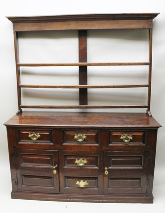 A GEORGE III OAK DRESSER BASE fitted three drawers across the top, above two small central drawers, flanked by panelled cupboard doors, replacement brass handles, on closed base, fitted shelf rack back, base - 168cm wide x 56cm deep x 94cm high, with top 210.5cm high