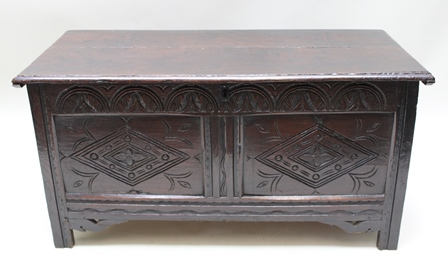 A GEORGIAN OAK COFFER, having plain plank lift-up lid, with later carved twin-panelled frontage, 58cm high x 114cm wide
