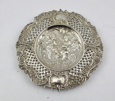 A 19TH CENTURY CONTINENTAL REPOUSSE AND PIERCED SILVER CARD TRAY, to the centre cherubs with musical instruments, import mark for 1892, 21cm diameter, 230g