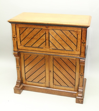 A LATE 19TH CENTURY AESTHETIC DESIGN LIGHT OAK FALL-FRONT WRITING BUREAU, with ebonised detail and decoration, the fall opens to reveal pigeon holes and fitted interior with leathered writing surfaces, the base fitted two cupboard doors, stamped Rumney & Love, Liverpool, 110cm high x 103cm wide