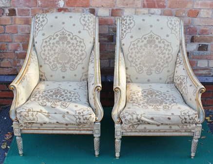 A PAIR OF 18TH CENTURY DESIGN FRENCH STYLE SCROLLING ARM EASY CHAIRS, upholstered in patterned cream fabric, on tapering spiral supports