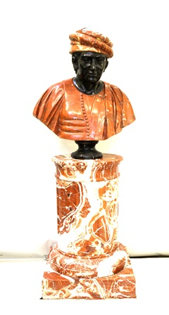 A 19TH CENTURY ROSSO ANTICO BUST OF MARCO POLO upon a veined rosso antico fluted column base, column stands 70cm, bust 69cm