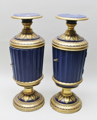 A PAIR OF 20TH CENTURY PAINTED AND GILT WOOD JARDINIERE STANDS, having fitted cupboards to the body, 89cm high