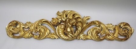 A 20TH CENTURY GILTWOOD ORNATELY CARVED BED OVERCREST, with cherub to the centre surrounded by acanthus leaves, 40cm high x 190cm wide
