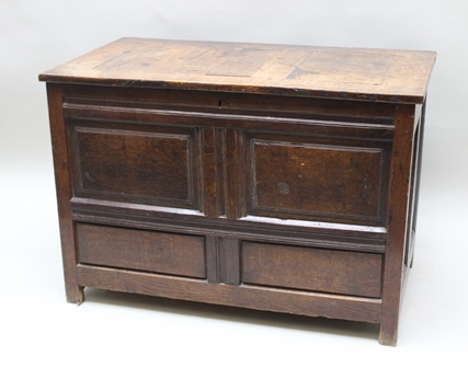 A 17TH CENTURY OAK COFFER, hinged cover over panelled carcase, raised on stile supports, 94cm wide x 66cm high x 50cm deep
