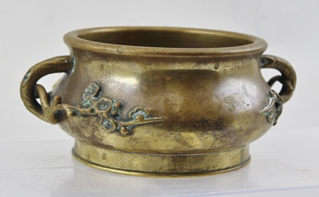 A BELIEVED 18TH CENTURY CHINESE CENSER with unusual cast spring blossom handles, on squat globular form with plain flared foot ring, the underside having cast Xuande six-character mark, 17cm at its widest