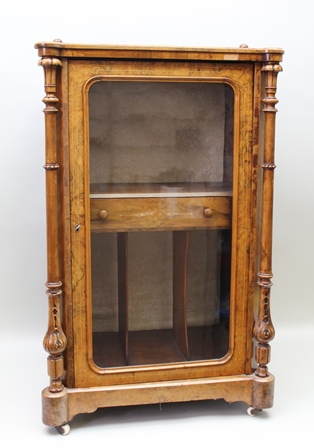 A VICTORIAN WALNUT INLAID MUSIC CABINET with cast brass bar gallery top, with decorative turned pilaster side supports flanking single plain glazed cupboard door revealing fitted interior, supported on white ceramic castors, 101cm high main carcase