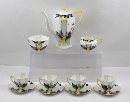 A SHELLEY ART DECO PART COFFEE SERVICE in the sunrise and tall trees pattern, (yellow and black colour), comprising coffee pot with lid, sugar bowl, cream jug and four cups with saucers.
