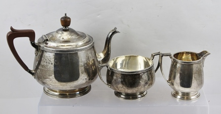 SELFRIDGE & CO LTD A 20TH CENTURY THREE-PIECE SILVER TEA SET,  comprising tea pot with hinged cover, milk jug and sugar bowl, decorative bands to rims, Birmingham 1927, total weight (including non silver teapot handle and knop) 1,120g