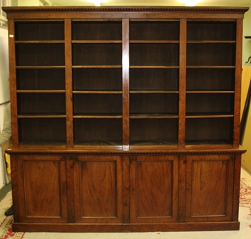 A VICTORIAN MAHOGANY LIBRARY BOOKCASE having fluted cornice over open adjustable shelves to the top in four section design, over a base fitted four cupboard doors, on plinth base, base 253cm wide, frieze 254cm wide, standing 239cm high