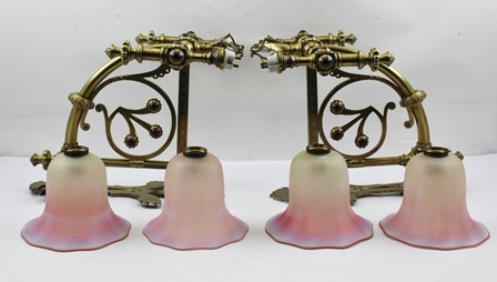 A PAIR OF BRASS GOTHIC REVIVAL WALL LIGHT FITTINGS, having decorative twin branch form set with red cabochons, complete with four pink opaque glass shades of flared rim bell form, the wall mounting back plates are 30cm high