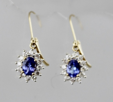 A PAIR OF GOLD TANZANITE AND DIAMOND CLUSTER EARRINGS with hoop fastenings