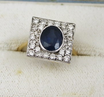 AN 18CT GOLD ART DECO STYLE SAPPHIRE AND DIAMOND RING, the central oval sapphire set within a square of mixed size diamonds, size N